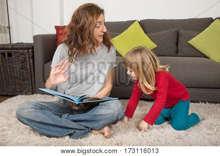 Woman Telling A Story To Child Sitting On Carpet