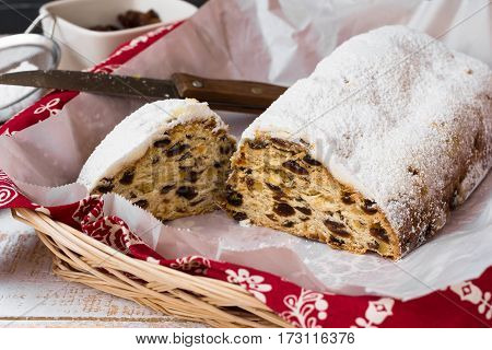 Homemade Christmas stollen with cut off slice with knife in wicker basket kitchen towel ingredients top view