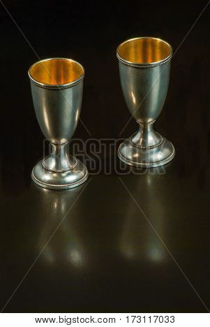 On a black background - two silver cups gilded inside. Retro noble form.