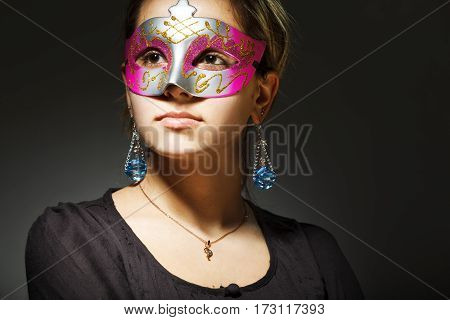 Portrait of beautiful young woman wearing carnival mask
