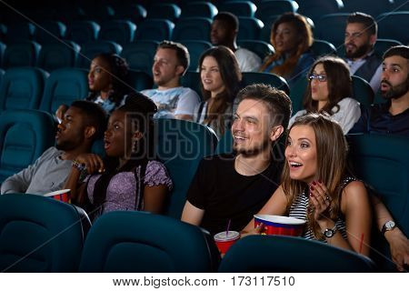 Unbelievable Shot of a beautiful young woman laughing excitedly while watching a movie with her boyfriend at the local cinema