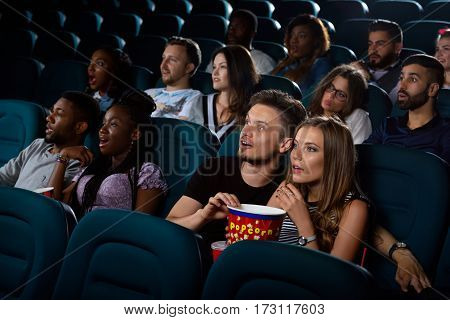 Best date entertainment. Portrait of a surprised young couple enjoying a movie at the cinema on their date night