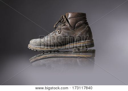 old used hiking or working boots with gray background