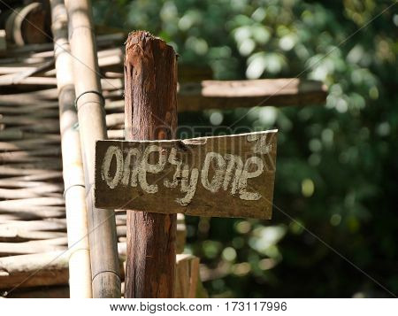 wooden sign directional signpost saying one by one in front of a wooden bamboo bridge