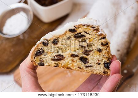 Woman's hand holding a piece of Christmas stollen loaf and ingredients in background top view close up