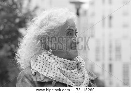 Portrait of an elegant old woman in the open air. Black and white.