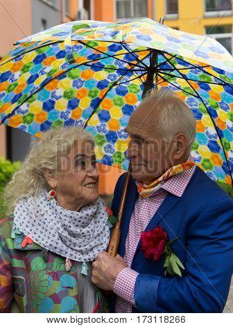 Elegantly dressed elderly couple walking and talking outdoors under an umbrella.