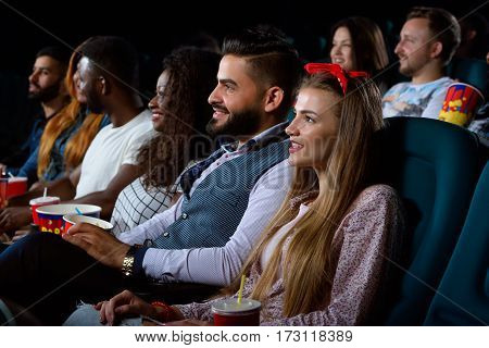 Waited for this movie forever. Portrait of a cheerful young woman relaxing at the cinema watching a movie together at the movie theatre