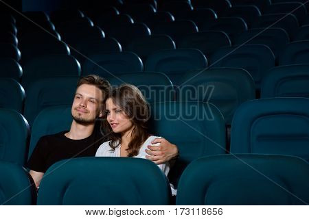 Lovebirds at the movies. Handsome young man hugging his beautiful girlfriend while enjoying a movie at the cinema in an empty cinema hall copyspace