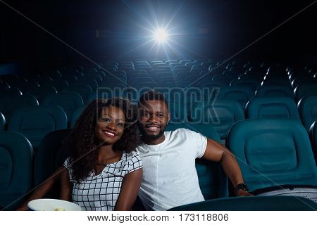Whole cinema to ourselves. Beautiful young cheerful African woman smiling happily while watching a movie with her boyfriend at the local cinema