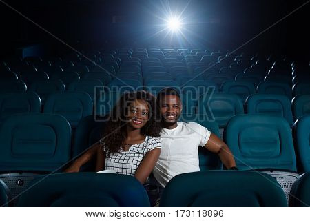 Whole cinema to ourselves. Shot of a joyful young beautiful African couple in love watching a movie in an empty cinema auditorium copyspace
