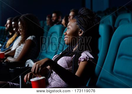 Best entertainment. Cheerful young African woman smiling while enjoying a movie at the local cinema