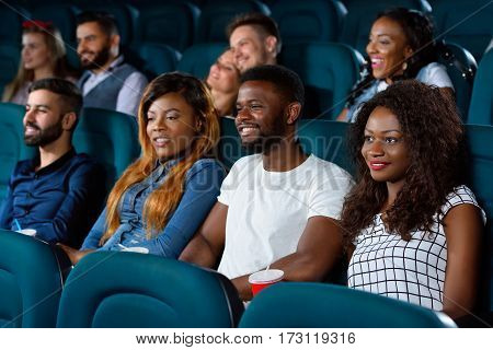 Fascination on point. Group of cheerful young friend looking interested while enjoying a movie at the local cinema