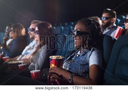 Thrilled to see this film. Shot of a cheerful African woman wearing 3D glasses while watching a movie at the cinema