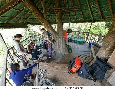 29 january 2017 gibbon experience huay xai laos, People standing watching sitting in a tree-house platform in the tree during the Gibbon Experience in Laos