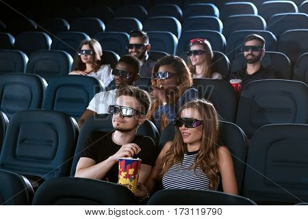 Sharing her snack. Beautiful young woman sharing popcorn with her handsome boyfriend while watching a 3D movie at the cinema
