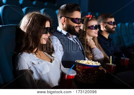 We always go together to the movies. Shot of a group of friends smiling cheerfully while watching a 3D movie together
