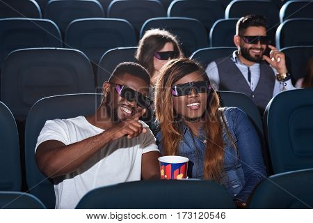 Attention on screen. Handsome African man pointing something out on a cinema screen to his beautiful girlfriend while watching a 3D movie together