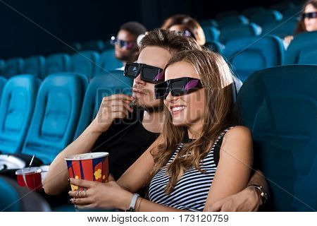 Movies with my girl. Shot of a handsome young man embracing his beautiful girlfriend while watching a 3D movie at the local cinema