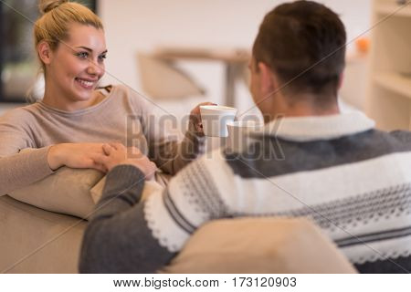 Young romantic couple sitting on sofa in front of fireplace at home, looking at each other, talking and drinking coffee at autumn day