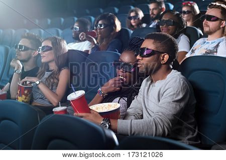 Classic snack. Portrait of a young woman eating popcorn while watching a movie with her boyfriend spectators wearing 3D glasses