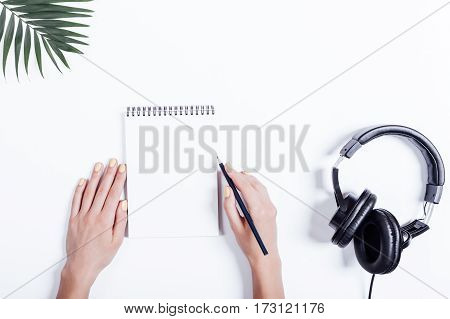 Female Hands, Notebook And Headphones On A White Table