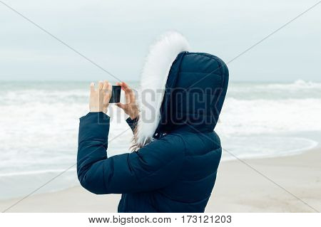 Woman In Winter Jacket With Hood Using A Mobile Phone On The Beach