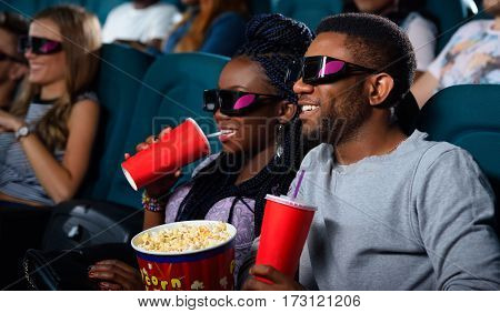 Drinks and corn Portrait of a cheerful African couple watching a 3D movie enjoying their drinks and popcorn