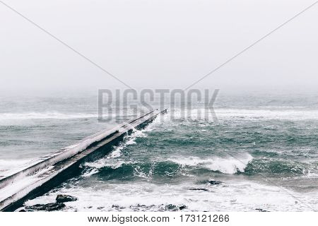 Concrete pier during snow fall gloomy landscape