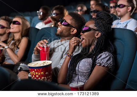 Chilling at the movies. Beautiful African woman in 3D glasses eating popcorn while on a date with her boyfriend at the cinema
