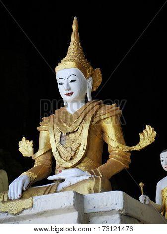 white golden buddha statue on black background