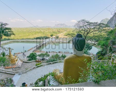 View from yathaypyan cave on surrounding landscape with back of buddha statue lake and surrounding hills and mountains