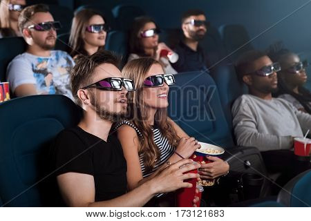 Entertained audience. Young couple in love enjoying a 3D movie together during their date at the cinema