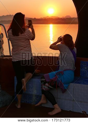04 february 2017, hpa-an, myanmar- two young women taking pictures of the sunset