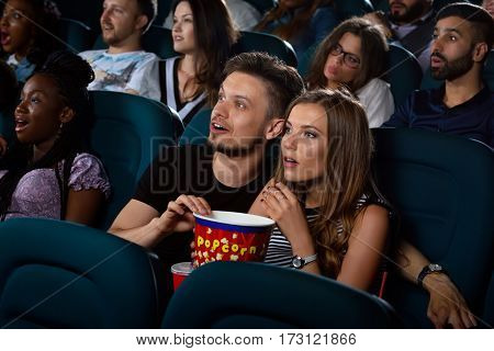 Lost their breath Young loving couple looking shocked as they are watching a movie at the local movie theatre together