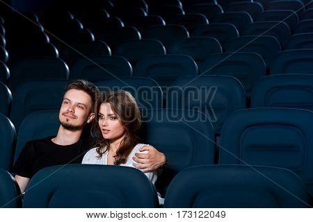 Getting all romantic. Beautiful young couple enjoying a movie in an empty cinema auditorium copyspace
