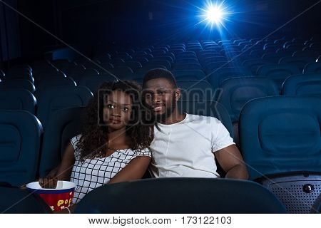 Relaxing date. Young beautiful African couple watching a movie hugging at the local cinema