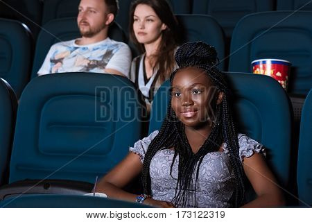Simple enjoyment. Shot of an attractive young woman watching a movie at the local movie theatre smiling happily copyspace on the side