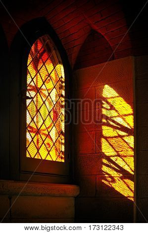 lights across stained colored glass with color reflections on the wall