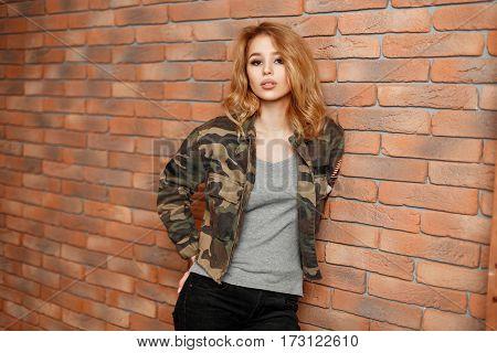 Beautiful Stylish Girl In Camouflage Jacket Near A Brick Wall