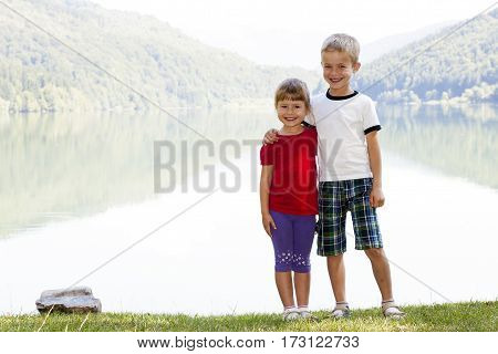 Happy smiling little boy and girl brother and sister standing hugging in sunny spring day near big lake in mountains