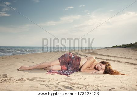 Red hair lady laying at the summer beach