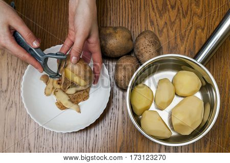 Detail Of Woman Hands Peeling Fresh Yellow Potato With Kitchen Peeler, Food Preparation Concept.
