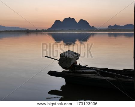 Motor and back of a long tail boat on a river side and tree leaves in front of an amazing colorful orange blue yellow calm and tranquil sunset without direct sunlight