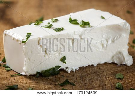 Close up of one piece of fresh feta cheese with herbs over wooden background