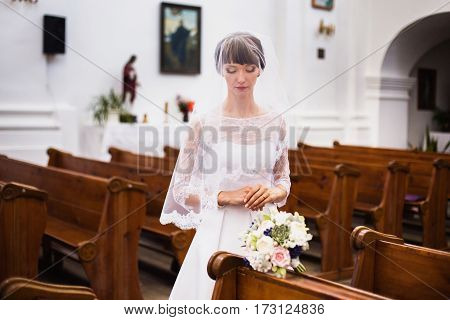 Bride in wedding dress. Beautiful bride in a white dress with a bouquet in the hands of the church. Wedding ceremony. Happy bride.