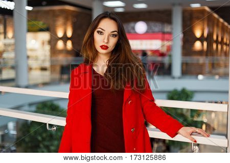 Young Beautiful Woman In A Red Coat Walking In Shopping Store