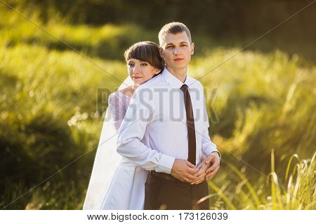 Strong hug with love. Happy groom and bride hug in a white dress on a background of nature. Wedding photography. Happy family hug