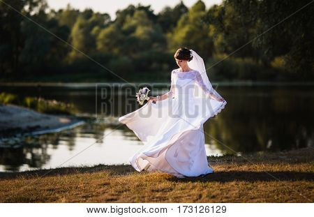 Long dress. The bride in a white wedding dress on nature background. Wedding photography. Woman in dress.