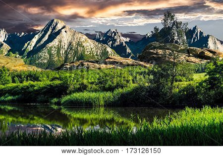 composite landscape with tree among tall grass on the shore of a lake at the foot of high mountains with rocky peaks under heavy clouds at sunset